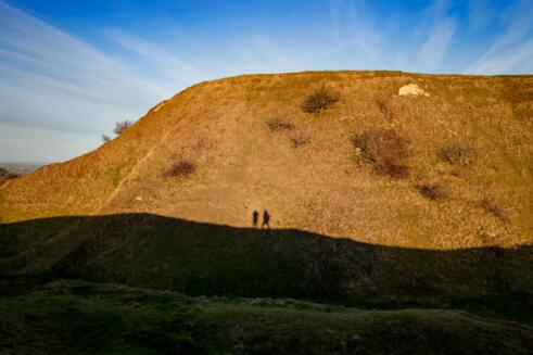 Two figures silhouetted against Cley Hill, Wiltshire, Uk